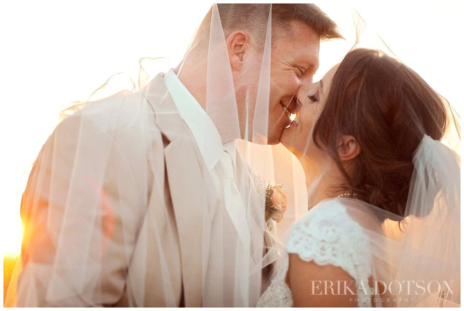 romantic sunset modern portrait of bride and groom covered by veil